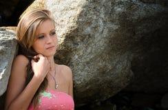 Pretty blue eyed, brunette girl in bikini against rocks Stock Image