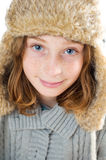 Pretty blue eyed girl wearing a winter hat. Twelve year old girl wearing a fuzzy winter hat close up studio shot Royalty Free Stock Photography