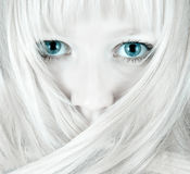 Pretty blue eyes. Covered by hair - shy blond portrait stock image