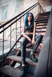 Pretty blue-haired rock girl informal model, dressed in black leather pants and topic, sits on stairway. Pretty blue-haired rock girl informal model, dressed in Stock Image