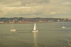 Pretty Boats Sailing In The Bay Seen From The Park Of Cimadevilla In Gijon. Nature, Travel, Holidays, Cities. stock photo
