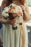 Pretty bouquet of peach and white ranunnculus is held by a tende Royalty Free Stock Images