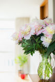 Pretty Bouquet of pink pale peonies in a glass jug with water on the table against the background of a bright room. Home decoratio Royalty Free Stock Photo