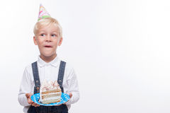 Pretty boy is celebrating his birthday with fun. Cheerful male child is standing and holding plate of tasty cake. He is licking his lips and smiling. The kid is Stock Photo