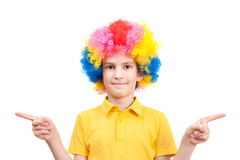 Pretty boy in clown dress pointing at sides Royalty Free Stock Images