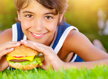 Pretty boy eat burger outdoors Stock Image