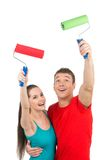 Pretty boy and girl using paint roller. Royalty Free Stock Photography