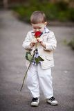 Pretty boy hold red rose in hand Stock Photo