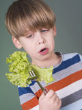 Pretty boy holding green salad on fork Stock Photos