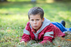 Pretty boy laying in grass at autumn season Royalty Free Stock Image