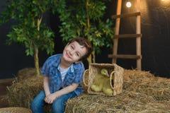 Pretty boy posing next to basket on the farm Stock Photo