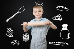 Pretty boy pretending to be a cook and holding a big rolling pin. Little chef. Cheerful little smiling boy holding a wooden rolling pin in his hands while Stock Photo