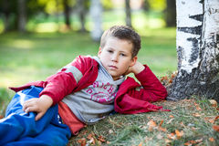 Pretty boy resting on autumn grass in park Royalty Free Stock Photos