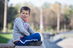 Pretty boy sitting lotus position on granite curb, copyspace Stock Photos