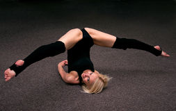 Pretty brawny girl. Happy pretty young sports girl smiling and doing splits on the floor Royalty Free Stock Image