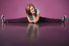 Pretty break dancer doing the splits. In the dance studio Stock Image