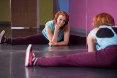 Pretty break dancer doing the splits looking in mirror. In the dance studio Stock Image