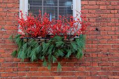 Pretty brick exterior wall of country home, with window box filled with Christmas cheer. Pretty background image of exterior brick wall of rural country home Royalty Free Stock Photography