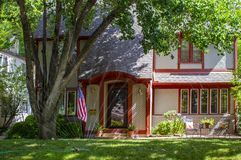 Pretty brick house trimmed in red with patio and flowers and big trees displaying American flag with watering sprinklers on grass Stock Photography