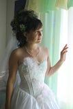 Pretty bride. Bride peers into window Royalty Free Stock Photography