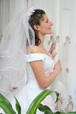 Pretty bride. Bride stand beside window and looks at street royalty free stock photo