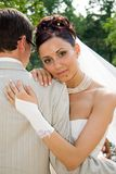 Pretty bride. Bride embraces bridegroom stock photo