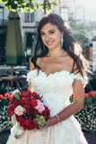 Pretty bride with charming smile hold the wedding bouquet of red and oink flowers. Outdoor portrait. Pretty bride with charming smile hold the wedding bouquet Royalty Free Stock Image