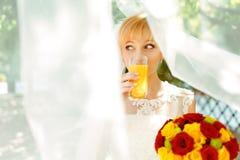 Pretty bride drinks orange juice standing under a veil Royalty Free Stock Image