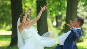 Pretty bride in elegant looking white dress and handsome groom have fun in park. Young woman pretend to slam her fiance stock footage