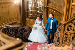 Pretty bride and handsome groom looking towards walking up old wooden stairs on the background of luxury interior Royalty Free Stock Image