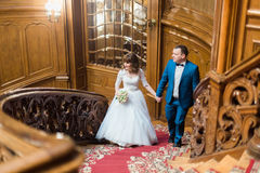 Pretty bride and handsome groom looking towards walking up old wooden stairs on the background of luxury interior Royalty Free Stock Photo