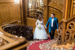 Pretty bride and handsome groom walking up old wooden stairs on the background of luxury interior Stock Photo