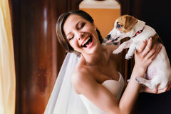 Pretty bride has fun while she plays with a dog.  Stock Images
