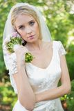 Pretty bride holding her bouquet wearing a veil Stock Photos