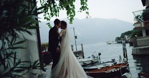 Pretty bride with long dress and the groom kissing and hugging each other in amazing place with lakeand boat beside stock video footage