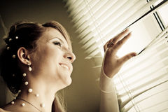 Pretty bride looking out of window Stock Photo