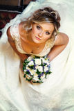 Pretty bride looks up thoughtful holding a bouquet of roses and Stock Photo