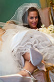 A Pretty Bride Lounging Backward in a Settee. A bride in her wedding dress sits to be photographed before her wedding Royalty Free Stock Images