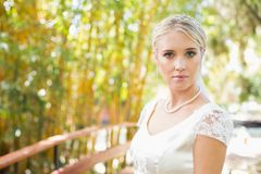 Pretty bride in pearl necklace standing on a bridge Royalty Free Stock Photo