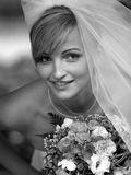 Pretty bride in portrait with veil. Beautiful bride in black and white portrait with traditional wedding dress and veil Royalty Free Stock Images