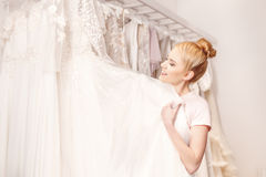 Pretty bride is selecting clothing in salon Stock Photography