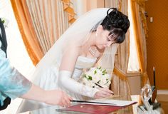 Pretty bride signing document Royalty Free Stock Photo