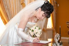 Pretty bride signing document Royalty Free Stock Photography