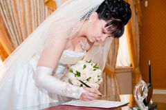 Pretty bride signing document Stock Photography