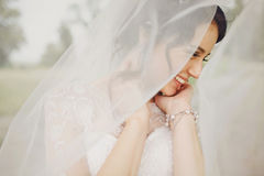 Pretty bride smiles shying under a veil stock photo