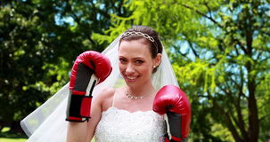 Pretty bride smiling at camera and wearing boxing gloves stock video