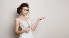 Pretty bride in wedding dress holding something on hand, smiling at camera. Brunette girl gesturing super sign by big finger and p Stock Photos