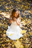 Pretty bride in white dress in sunny autumn park Royalty Free Stock Photography
