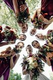 Pretty bridesmaids surround a bride holding wedding bouqeuts in their arms. Bride with bridesmaids on the park on the wedding day stock photo