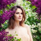 Pretty brown-haired girl with layered hair haircut in flowers outdoor.  stock images